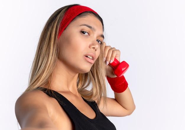 검은 운동복과 흰 벽 위에 서있는 자신감이있는 식으로 아령을 들고 빨간 머리띠에 젊은 피트니스 소녀
