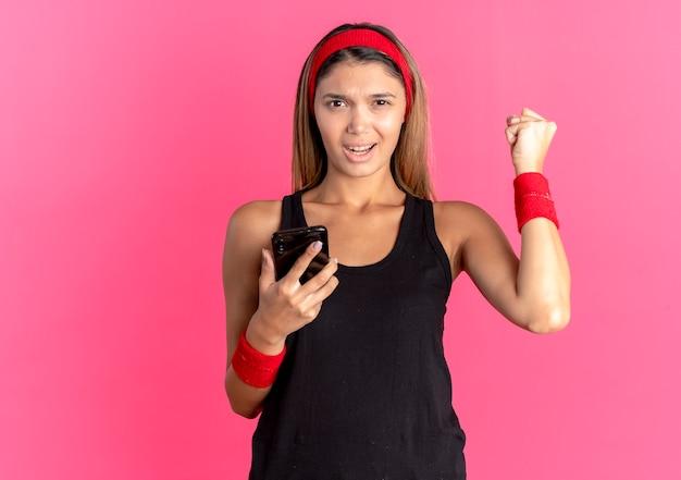ピンクの壁の上に立って幸せで興奮した拳を握りしめるスマートフォンを保持している黒いスポーツウェアと赤いヘッドバンドの若いフィットネスの女の子