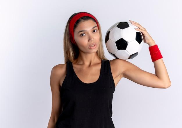 흰색 벽 위에 서 심각한 얼굴로 어깨에 축구 공을 들고 검은 운동복과 빨간 머리띠에 젊은 피트니스 소녀
