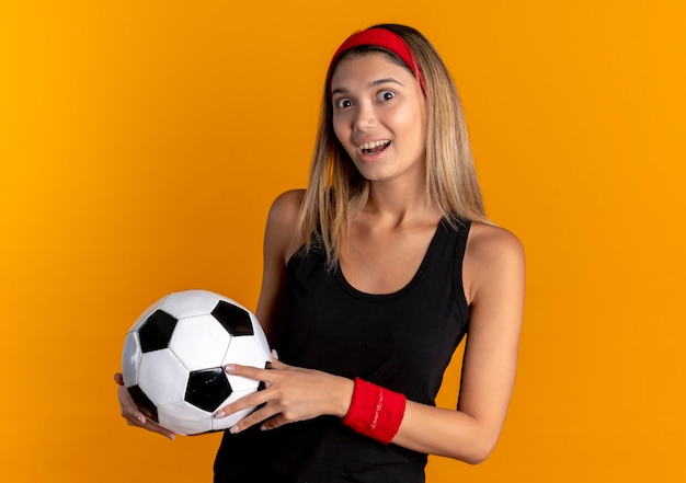 오렌지를 통해 행복한 얼굴로 놀란 검은 운동복과 축구 공을 들고 빨간 머리띠에 젊은 피트니스 소녀