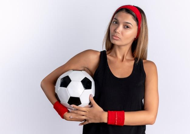 흰색 벽 위에 서 심각한 얼굴로 축구 공을 들고 검은 운동복과 빨간 머리띠에 젊은 피트니스 소녀