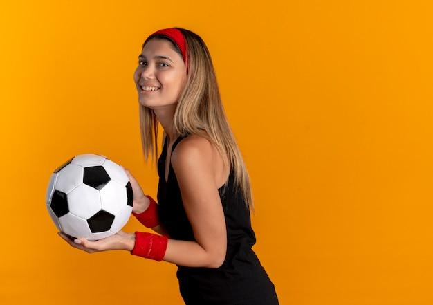 오렌지 벽 위에 서있는 얼굴에 미소로 축구 공을 들고 검은 운동복과 빨간 머리띠에 젊은 피트니스 소녀