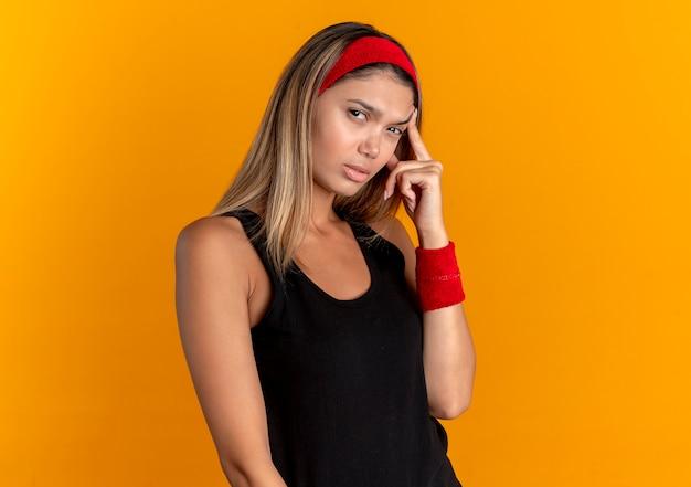 그녀의 사원에서 손가락으로 가리키는 검은 색 운동복과 빨간 머리띠에 젊은 피트니스 소녀는 오렌지 벽에 열심히 서서