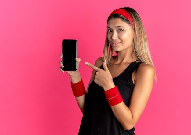 검은 운동복과 빨간 머리띠에 젊은 피트니스 소녀가 분홍색 위에 미소 짓는 손가락으로 스마트 폰 pointign을 보여주는