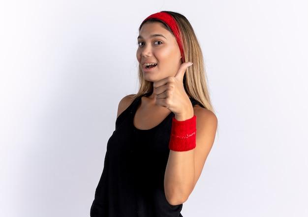 검은 운동복과 빨간 머리띠에 젊은 피트니스 소녀 흰색 벽 위에 서 엄지 손가락을 보여주는 미소