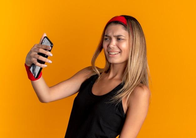 검은 색 운동복과 빨간 머리띠에 젊은 피트니스 소녀가 스마트 폰을 사용하여 셀카를 복용하고 주황색 벽 위에 서서 불쾌감을 느낍니다.