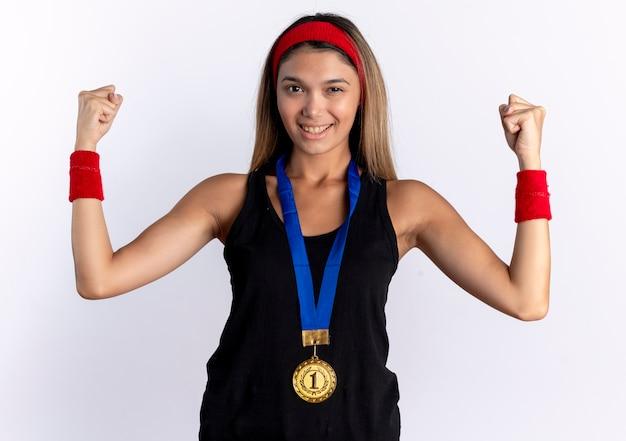 검은 운동복에 젊은 피트니스 소녀와 목 주위에 금메달이 달린 빨간 머리띠가 주먹을 행복하고 긍정적으로 윙크하고 흰 벽 위에 서서 웃고 있습니다.