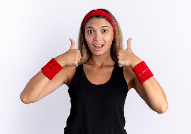 흰색 벽 위에 서 엄지 손가락을 보여주는 행복한 얼굴로 검은 운동복과 빨간 머리띠에 젊은 피트니스 소녀