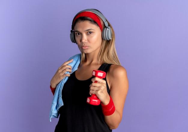 파란색 벽 위에 서 심각한 얼굴로 아령을 들고 헤드폰 검은 운동복과 빨간 머리띠에 젊은 피트 니스 소녀