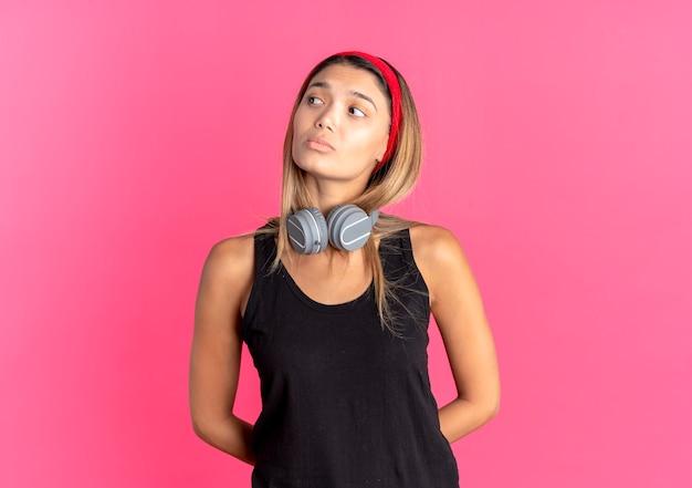 Молодая фитнес-девушка в черной спортивной одежде и красной повязке на голову с наушниками смотрит в сторону, смущенная грустным выражением лица над розовым