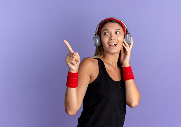 검은 색 운동복과 파란색 벽 위에 서있는 측면을 손가락으로 가리키는 헤드폰이있는 빨간 머리띠에 젊은 피트니스 소녀