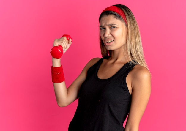 Молодая фитнес-девушка в черной спортивной одежде и красной повязке на голове тренируется с гантелями и выглядит смущенной, стоя у розовой стены