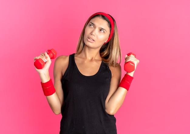 검은 색 운동복과 빨간 머리띠에 젊은 피트니스 소녀는 옆으로 분홍색 벽 위에 의아해 서 찾고 아령으로 운동