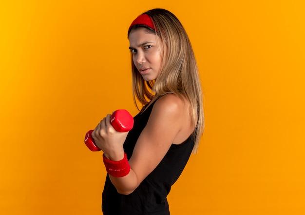 검은 운동복과 빨간 머리띠에 젊은 피트니스 소녀는 오렌지 위에 자신감을 찾고 아령으로 운동