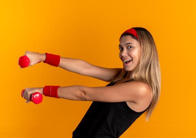 검은 운동복과 빨간 머리띠에 젊은 피트니스 소녀는 오렌지 위에 유쾌하게 웃는 아령으로 운동