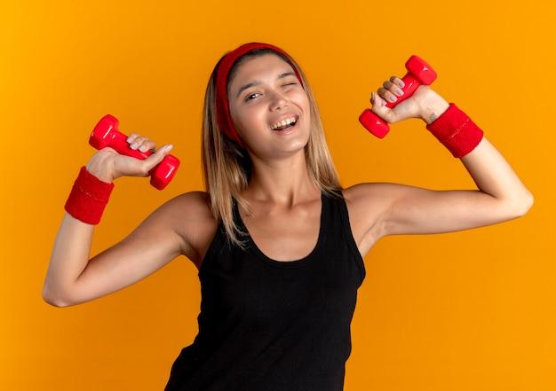 オレンジ色の壁の上に元気に立って笑っているダンベルと一緒に運動している黒いスポーツウェアと赤いヘッドバンドの若いフィットネスの女の子