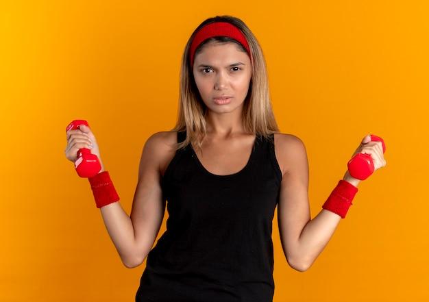오렌지 벽 위에 서 심각한 얼굴로 아령으로 운동 검은 운동복과 빨간 머리띠에 젊은 피트니스 소녀