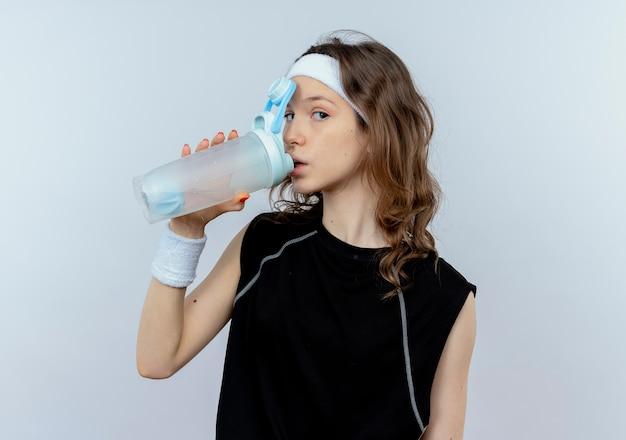 白い壁の上に立っているトレーニング後の黒いスポーツウェア飲料水で若いフィットネスの女の子
