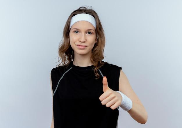 검은 운동복에 젊은 피트니스 소녀 흰색 벽 위에 서 웃고 엄지 손가락을 보여주는