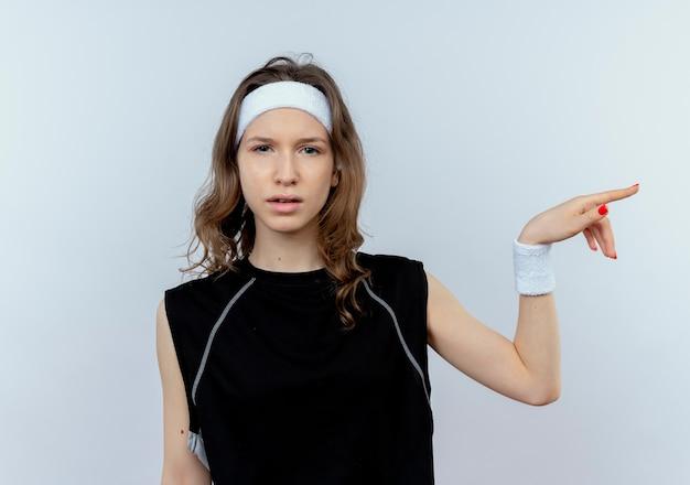 Молодая фитнес-девушка в черной спортивной одежде с растерянным выражением лица, указывая пальцем в сторону, стоящую над белой стеной