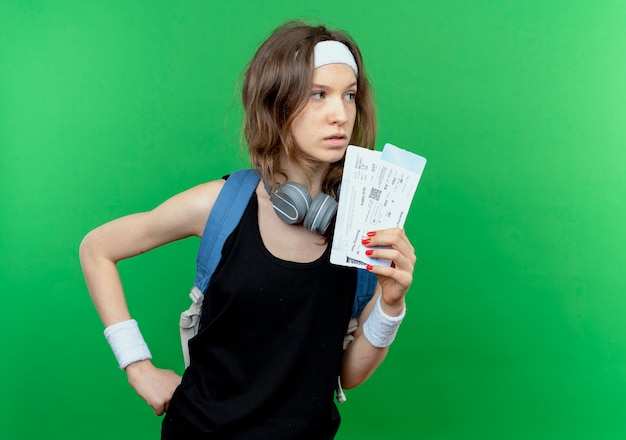 머리띠와 배낭 녹색 벽 위에 서 심각한 얼굴로 옆으로 찾고 항공 티켓을 들고 검은 운동복에 젊은 피트니스 소녀