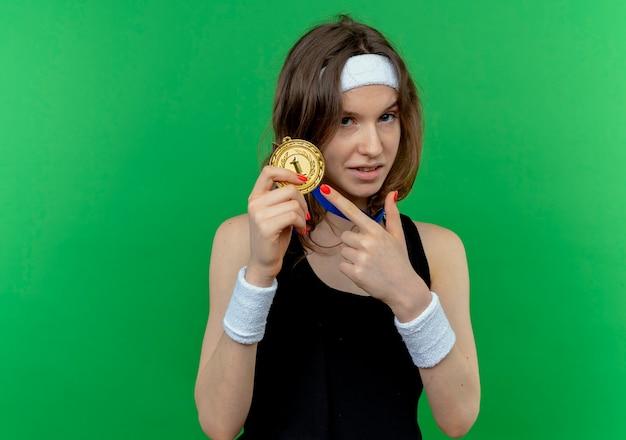 녹색 벽 위에 자신감 서 찾고 그것에 손가락으로 가리키는 목 주위에 머리띠와 금메달과 검은 운동복에 젊은 피트니스 소녀 무료 사진
