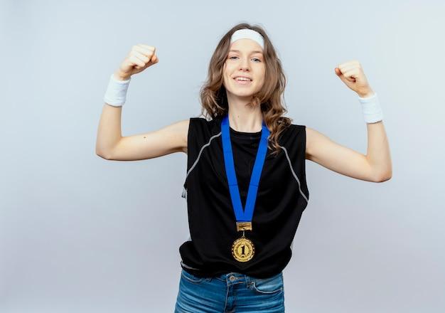 머리띠와 목에 금메달이 달린 검은 색 운동복에 젊은 피트니스 소녀가 흰 벽 위에 자신감이 서있는 승자처럼 주먹을 올리는 목