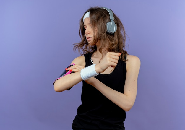 青い壁の上に立っている彼女のスマートフォンの腕章を固定する彼女の手に触れるヘッドバンドとヘッドフォンを持つ黒いスポーツウェアの若いフィットネスの女の子