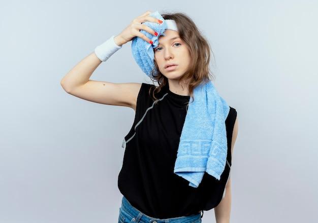 Молодая фитнес-девушка в черной спортивной одежде с повязкой на голову, наушниками и полотенцем на плече выглядит усталой, вытирая лоб, стоя над белой стеной