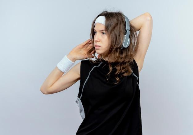 머리띠와 헤드폰 흰색 벽 위에 자신감 서 찾고 그녀의 손을 뻗어 검은 운동복에 젊은 피트니스 소녀
