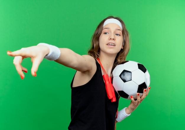 ヘッドバンドと緑の壁の上に立っている指で何かを指しているサッカーボールを保持している首の周りの縄跳びと黒いスポーツウェアの若いフィットネスの女の子
