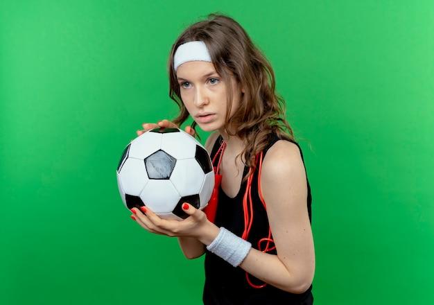 緑の壁の上に立っている真剣な表情で見てサッカーボールを保持しているヘッドバンドと首の周りの縄跳びと黒いスポーツウェアの若いフィットネスの女の子