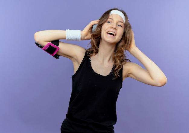 Молодая фитнес-девушка в черной спортивной одежде с повязкой на голову и повязкой для смартфона смотрит в сторону, весело улыбаясь, стоя у синей стены