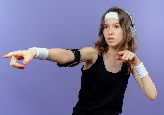 파란색 벽 위에 서있는쪽에 검지 손가락으로 가리키는 머리띠와 스마트 폰 완장 검은 운동복에 젊은 피트니스 소녀