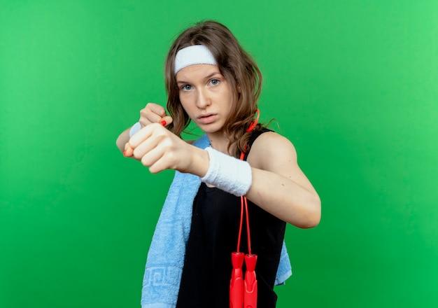 緑の壁の上に立っているボクサーのようにくいしばられた握りこぶしで肩にヘッドバンドとタオルを備えた黒いスポーツウェアの若いフィットネスの女の子