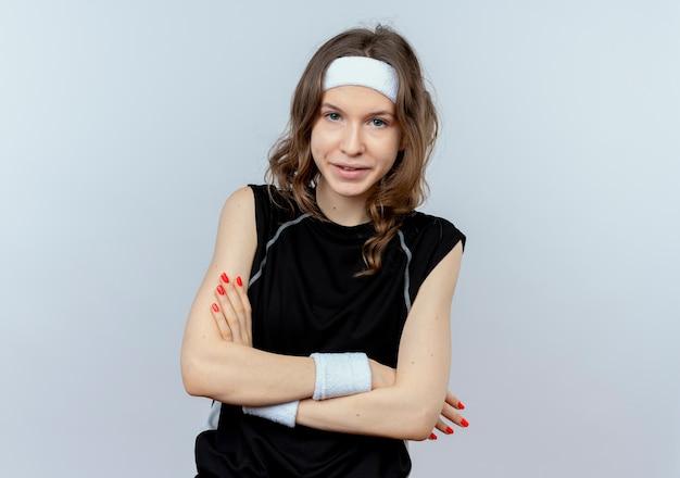 머리띠가 흰색 벽 위에 서서 불쾌하고 혼란스러워하는 검은 색 운동복에 젊은 피트니스 소녀