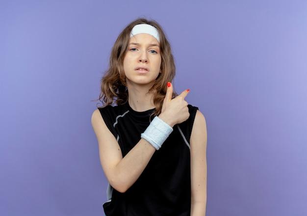 青い壁の上に立って後ろを向いて不機嫌なヘッドバンドを持つ黒いスポーツウェアの若いフィットネスの女の子