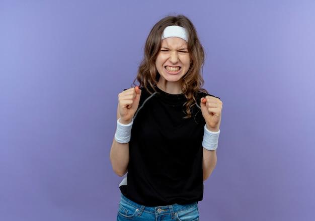 머리띠와 검은 운동복에 젊은 피트니스 소녀는 파란색 벽 위에 서있는 야생 떨림 주먹을가는 좌절