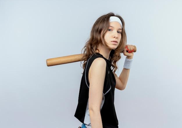 흰색 벽 위에 서 심각한 얼굴로 basaball 방망이 들고 머리띠와 검은 운동복에 젊은 피트니스 소녀
