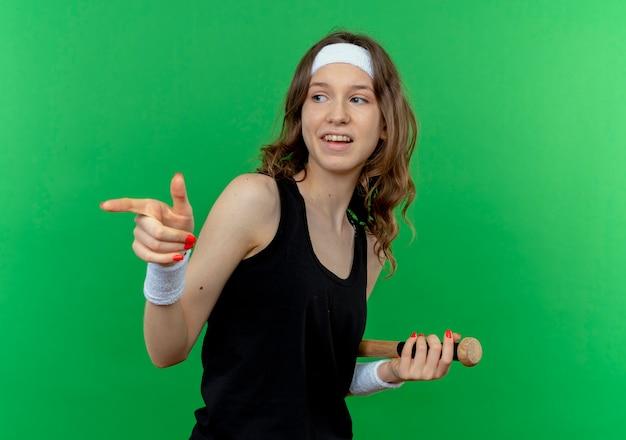 녹색 벽 위에 서있는 측면에 검지 손가락으로 가리키는 야구 방망이를 들고 머리띠와 검은 운동복에 젊은 피트니스 소녀