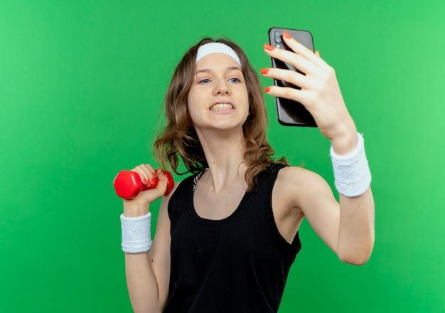 緑の壁の上に立っているスマートフォンを使用してselfieを作る手にダンベルを保持しているヘッドバンドと黒のスポーツウェアの若いフィットネスの女の子
