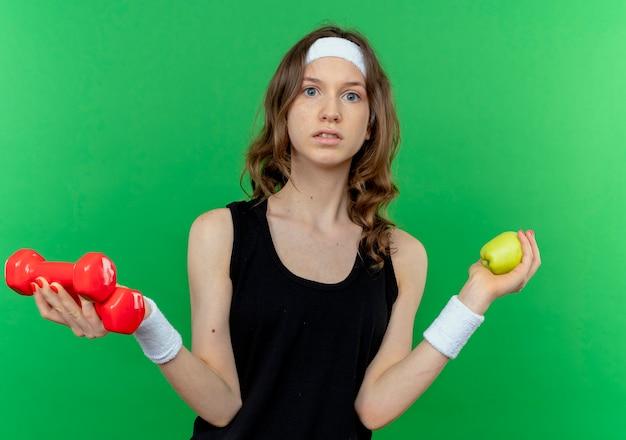 ダンベルを保持しているヘッドバンドと緑の壁の上に立って混乱しているように見える青リンゴと黒のスポーツウェアの若いフィットネスの女の子