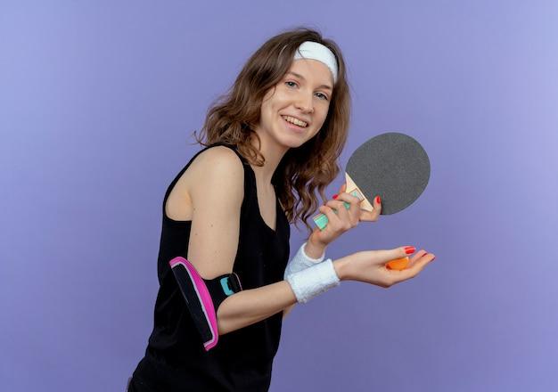 Молодая фитнес-девушка в черной спортивной одежде с повязкой на голову, держащей ракетку и мячи для настольного тенниса, готова играть, весело улыбаясь, стоя у синей стены