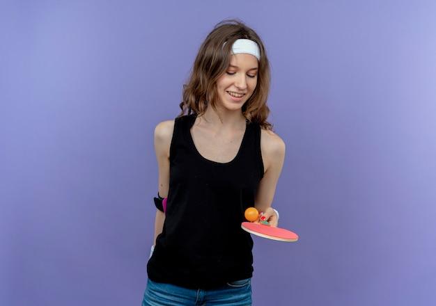 Молодая фитнес-девушка в черной спортивной одежде с повязкой на голову держит ракетку и мячи для настольного тенниса, бросая мяч, улыбаясь, стоя над синей стеной