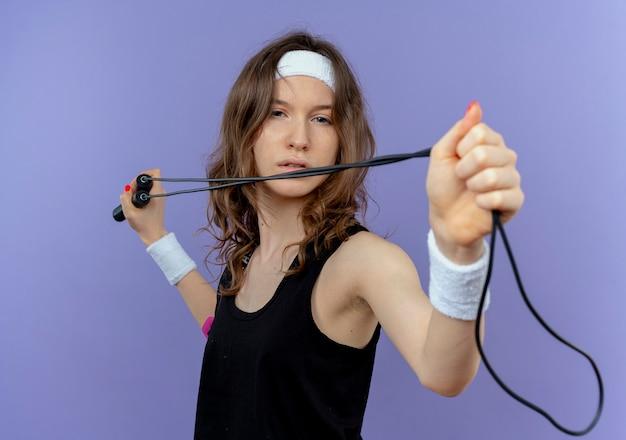 青い壁の上に立っている矢印と弓で狙うように縄跳びを保持しているヘッドバンドを持つ黒いスポーツウェアの若いフィットネスの女の子
