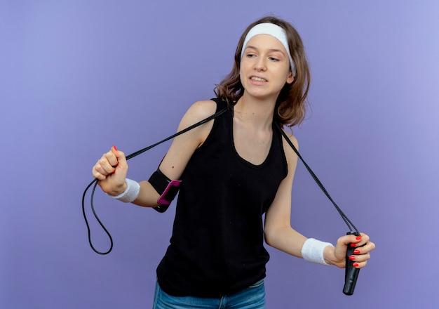 青い壁の上に立って自信を持って縄跳びを保持しているヘッドバンドを持つ黒いスポーツウェアの若いフィットネスの女の子