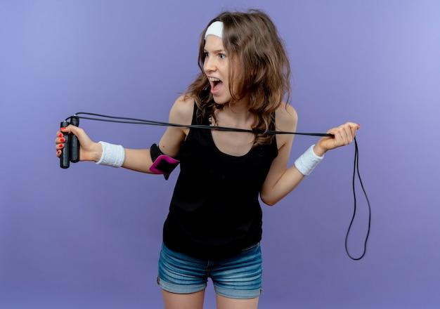 青い壁の上に立って怖い脇を見て縄跳びを保持しているヘッドバンドを持つ黒いスポーツウェアの若いフィットネスの女の子