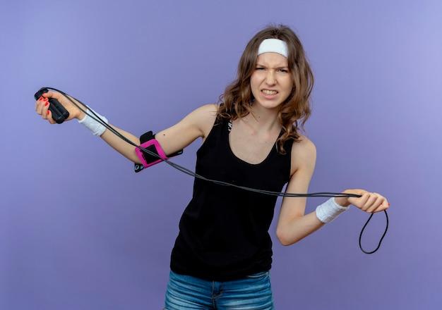 青い壁の上に立って混乱し、不快に見える縄跳びを保持しているヘッドバンドを持つ黒いスポーツウェアの若いフィットネスの女の子