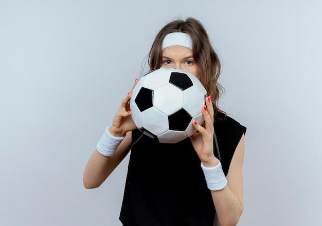 흰색 벽 위에 서있는 그녀의 얼굴을 숨기는 축구 공을 들고 머리띠와 검은 운동복에 젊은 피트니스 소녀