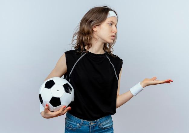 Молодая фитнес-девушка в черной спортивной одежде с повязкой на голову, держащая футбольный мяч, смотрит в сторону с вытянутой рукой и спрашивает, стоя у белой стены